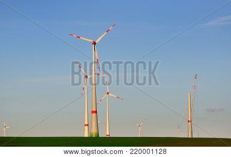 Wins generators against blue sky, wind generator under construction.