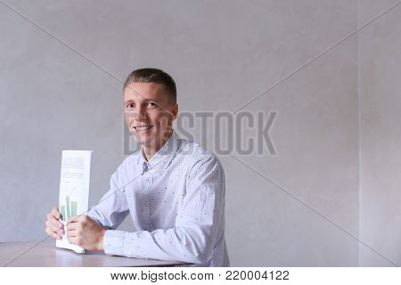 Entrepreneur looking into camera and smiling, completes work day. Men with short hair and blond hair sitting on chair at white table in office and dressed in white classic shirt. Concept of businessman office work, sedentary routine work documentation, su