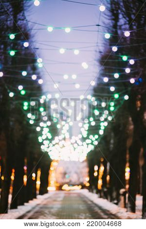 Riga, Latvia. Abstract Blurred Bokeh Boke Background Of Evening Esplanade Park On Freedom Street Decorated With Festive Christmas Xmas New Year Illuminations.