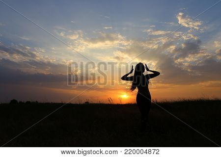 Female with beautiful figure takes yoga postures, gymnastics and ballet spends stretching and meditating, posing for advertising shoot fitness studio, healthy energy drink, dancing belly dancing among wide field on background of yellow sunset and beautifu