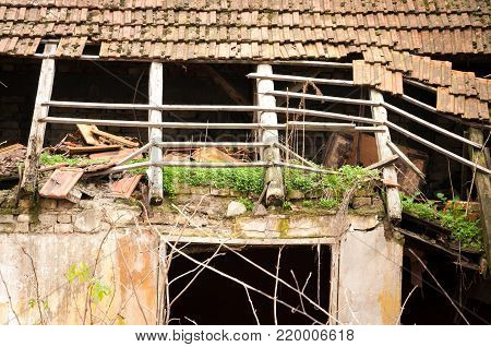 Old abandoned house with damaged roof tiles and hole instead of windows destroyed by hurricane and left to collapse