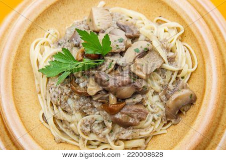 a crock dish with tagliatelle and mushrooms