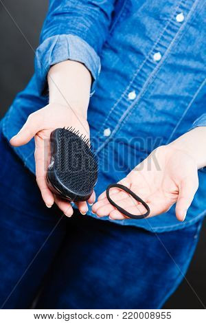 Everyday morning routine. Female hands with black comb hairbrush and elastic hair. Woman with barber equipment.