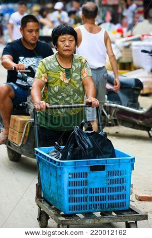 SUZHOU, CHINA September 1 2017: Woman pushing a trolley at a market in Suzhou China
