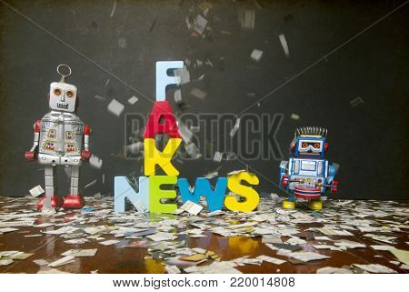 newspaper confetti comes down on the word FAKE NEWS  with two retro robot toys on a wooden floor