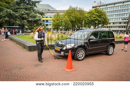 THE HAGUE, NETHERLANDS. July 19, 2017. Woman guard checking the car bottom for possible explosives at the gate of the Peace palace in central Hague.