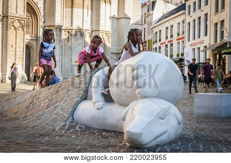 ANTWERP, BELGIUM. July 17, 2017. Three little African girls playing on a statue of a boy Nello and his dog Patrasche by the Antwerp Cathedral. They are characters of a novel