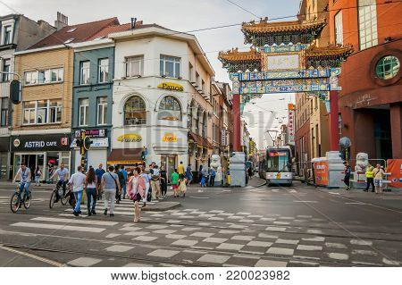 ANTWERP, BELGIUM. July 18, 2017. Tram going through the Chinese gateway (Paifang) on Carnotstraat street in front of the Antwerp central station.