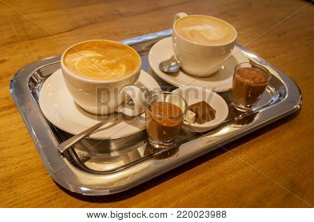 Two cups of cappuccino on a steel tray with chocolate mousse and a small chocolate on the side. Coffee and chocolate meal in a coffee shop. Drawing on coffee foam.