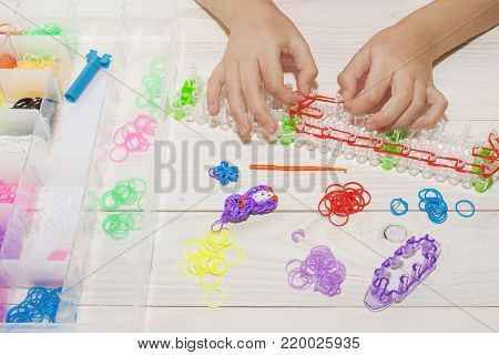 Girl's hand with wristbands and rings made of rubber bands Rainbow loom Colored rubber bands for weaving