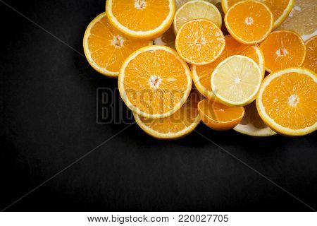 Citrus fruits (orange, lemon, grapefruit, mandarin, lime) on the dark background. Fruit food background. Fresh citrus fruit assortment