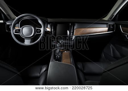 Dark luxury car Interior - steering wheel, shift lever and dashboard. Car interior luxury. Beige comfortable seats, steering wheel, dashboard, climate control, speedometer, display and wood panels