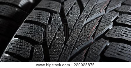 Brand new winter tires with a modern tread and water drops