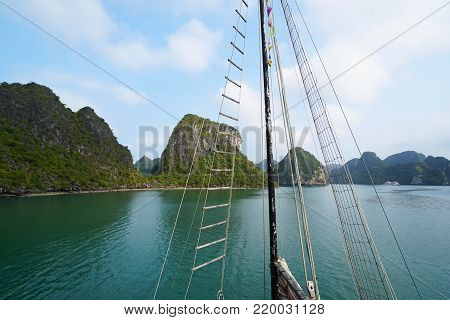 Ha Long Bay, Vietnam. In the foreground are rope lines of a large boat forming a triangle. Background is the mountainous terrain behind green water. The sky is blue with light clouds. Unusual mountain land formations. UNESCO world Heritage site of Ha Long