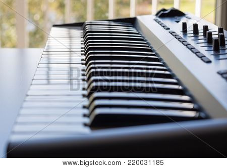 An electronic keyboard is in a bright room placed next to an open window. This is a bright image with the focus being on the keyboards ivory keys. The keyboard has a control board built in.