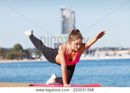 Woman doing sports outdoors. Fitness girl in sportswear on seaside exercising keep her body muscles fit