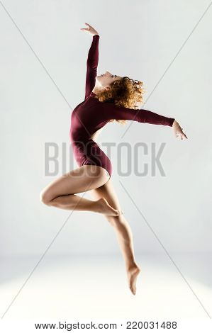 Beautiful Young Professional Dancer Dancing Over White Background.