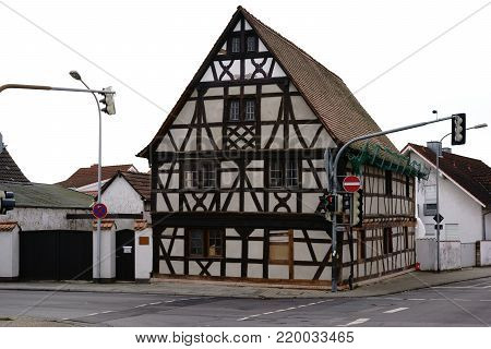 A half timbered house with a striking beam construction at the corner of a crossroads.