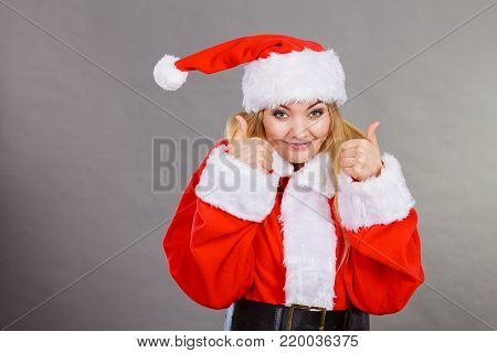Xmas, seasonal clothing, winter christmas concept. Happy woman wearing Santa Claus helper costume showing thumb up gesture.