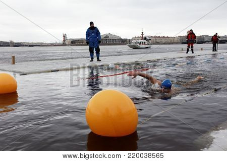 ST. PETERSBURG, RUSSIA - MARCH 18, 2017: People participate in the winter swimming competitions in river Neva at St. Peter and Paul fortress. The event aimed to revive the winter swimming tradition