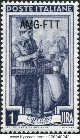 ITALY - CIRCA 1950: A stamp printed in Italy, shows the Auto mechanic, in the background Sacra di San Michele, Florence, (Piedmont), (overprint «AMG FTT» - allied military government. Free Territory of Trieste), circa 1950