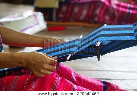 Traditional Thai weaving process. The weaving of a scarf in progress. An older woman's hands work on a blue and black textile. Her work rests in her lap with colorful fuchsia pink pants. Thailand artisan.
