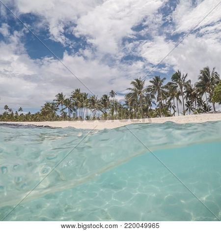 Split view of beautiful beach on Upolu Island in Western Samoa with palm trees and clear transparent turquoise sea of South Pacific ocean. Taken with underwater dome while snorkeling on vacation.