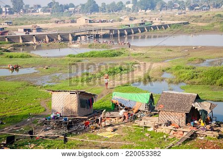 Mandalay, Myanmar - 2016, December 26 : A river scene with shacks and people on the waterfront and crossing the river Irrawaddy on a bridge