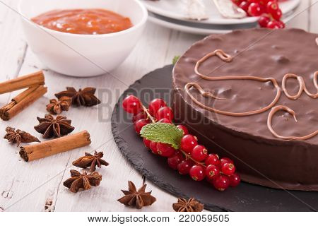 Sacher torte with jam on black dish.