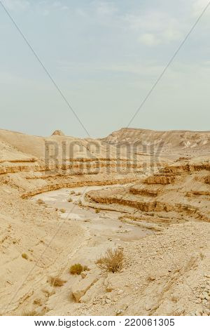 View from mountain on dry middle east wilderness in Israel. Valley of sand, rocks and stones. Scenic outdoor landscape view on desert. Summer heat sunlight with nobody on photo