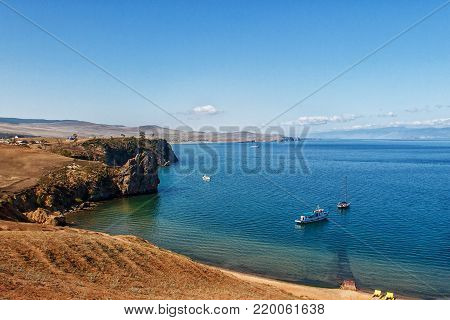 Landscape with the image of the rocky coast of lake Baikal and boats. A view of the lake from the island Khuzhir