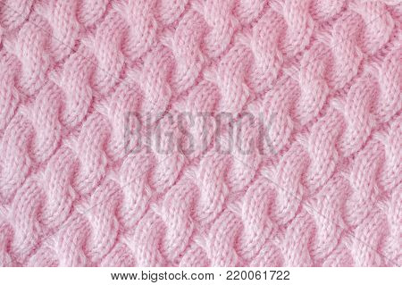 Knitted fabric made of wool yarn pink color. Pattern