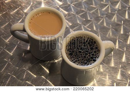 Two cups of coffee, one with cream and sugar, the other black, set on  metal table with interesting design.