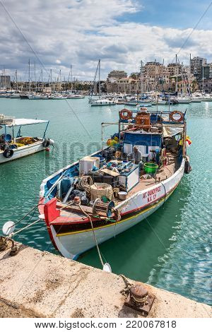 Heraklion, Greece - November 2, 2017: Fishing boat and a fisherman with a dog in the port of Heraklion, Crete, Greece.