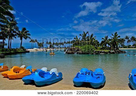 Honolulu, HI,USA - July 5, 2015: Paddle boats on the beach of the Duke Kahanamoku Lagoon at the Hilton Hawaiian Village.The Lagoon is very popular by families.