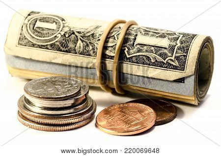 close up of  dollar bill roll and coin in pile over a white background. symbol of wealth