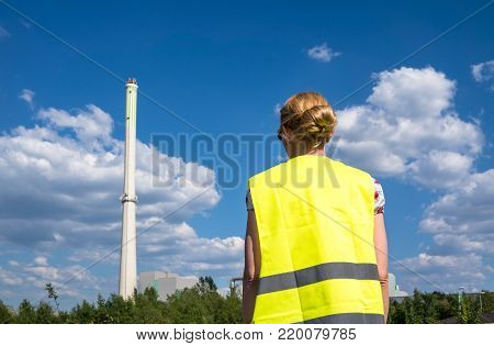 Blond lady observing a garbage incineration plant