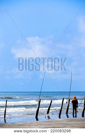 Solitary fisherman on the beach anticipating a catch.