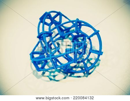 Abstract object of a blue color printed by 3d printer on white background. Fused deposition modeling, FDM. Progressive modern additive technology. Concept of 4.0 industrial revolution