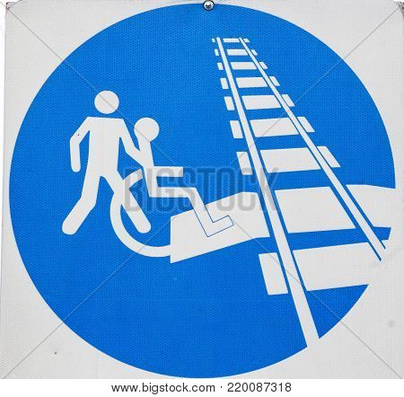 Warning sign for crossing the railroad tracks on the disabled wheelchair only when accompanied.