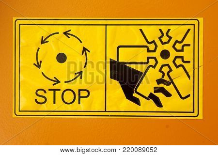 Warning sign on agricultural machinery. Do not touch the moving parts of the machine until they are completely stopped.