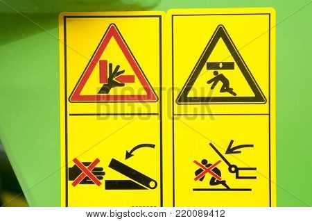 Warning sign on agricultural machinery. Before working under the sloping chamber is necessary to fix the lifting cylinders. Caution possible damage to the hand. Be careful.
