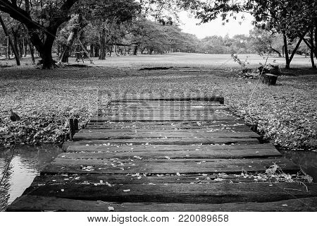 Black and White image of old wooden bridge cross over the river in the park.