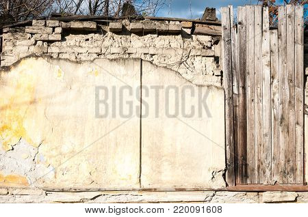 Close up of old demolished and abandoned house exterior wall with wooden boards nailed on the windows without roof