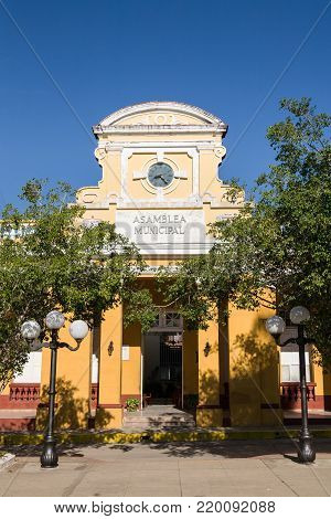 The facade of the city hall building in the Cespedes square of Trinidad in Cuba with the writing City Assembly (Asamblea Municipal)