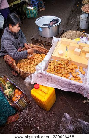 Nyaungshwe, Myanmar - 2017, January 4 : A female hawker or vendor selling Burmese tofu and tofu fritters in a street market in the town of Nyaungshwe on the Inle Lake of central Burma