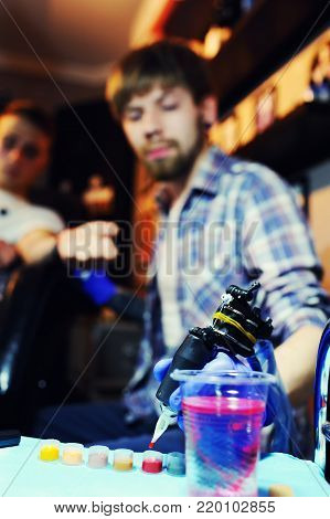 tattoo artist makes a new tattoo to a young guy on his arm in a tattoo parlor