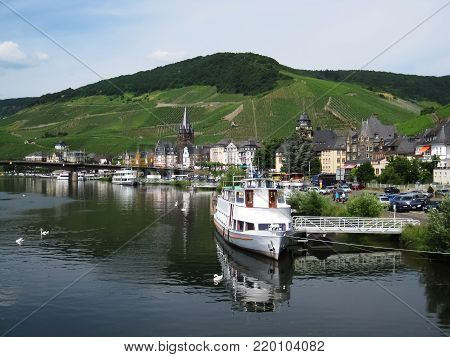 White tourist ship in dock and green vineyard hill in background
