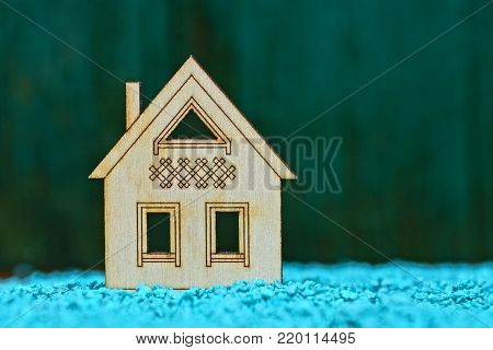 A small breadboard model of a wooden house on small blue stones on a green background