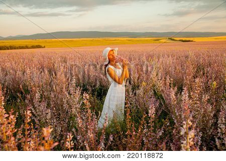 A girl in a white dress and hat walks the field of sage